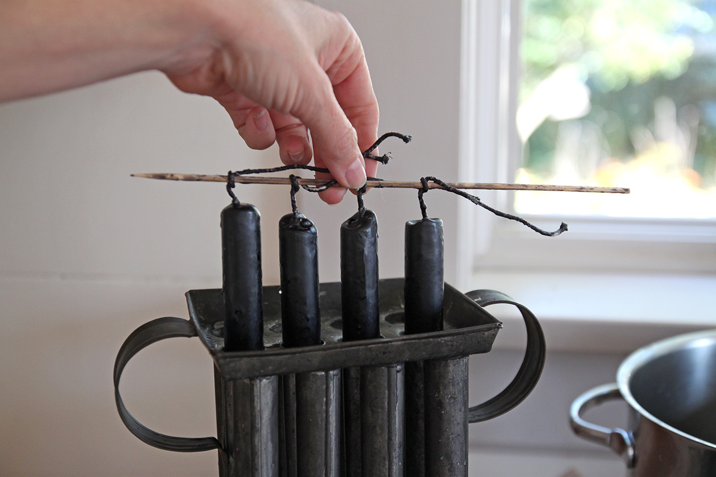black beeswax candles DIY, taking from mold, by Justine Hand for Remodelista